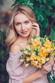 Portret van glimlachende blonde jonge vrouw die gele bloemen houdt