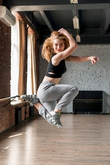 Portret van glimlachende blonde jonge vrouw die in de lucht springt