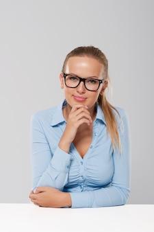 Portret van glimlachende blonde onderneemster die manierglazen draagt