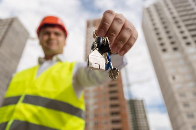 Portret van glimlachende bouwingenieur die sleutels van nieuw huis toont
