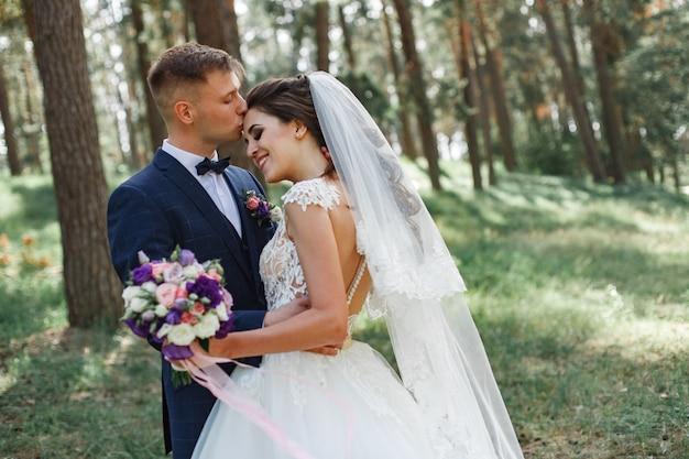 Portret van glimlachende bruid en bruidegom wandelen in het park in zonnige zomerdag. zachte omhelzing van gelukkige pasgetrouwden over de natuur.