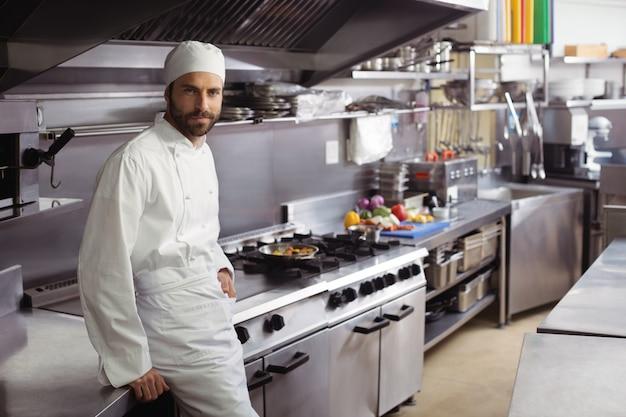 Portret van glimlachende chef-kok die zich in commerciële keuken bevindt