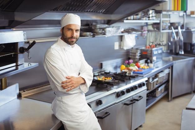 Portret van glimlachende chef-kok die zich met wapens bevindt die in commerciële keuken worden gekruist