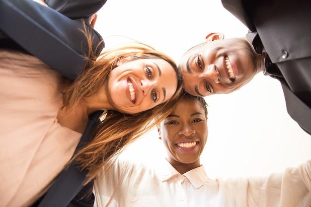 Portret van glimlachende collega's die en camera omhelzen bekijken