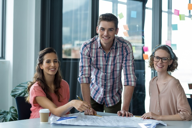 Portret van glimlachende directeuren met blauwdruk op tafel