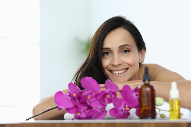 Portret van glimlachende donkerbruine vrouw in kuuroordcentrum. diensten en diensten in het concept van schoonheidssalons