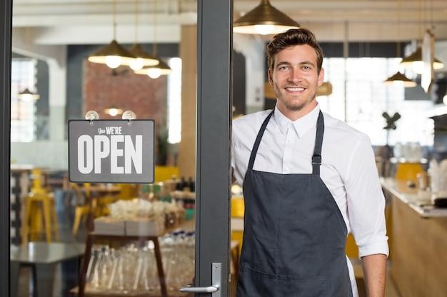 Portret van glimlachende eigenaar die zich bij zijn restaurantpoort met open uithangbord bevindt