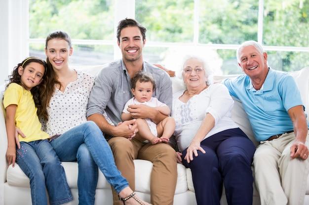 Portret van glimlachende familie met grootouders terwijl het zitten op bank