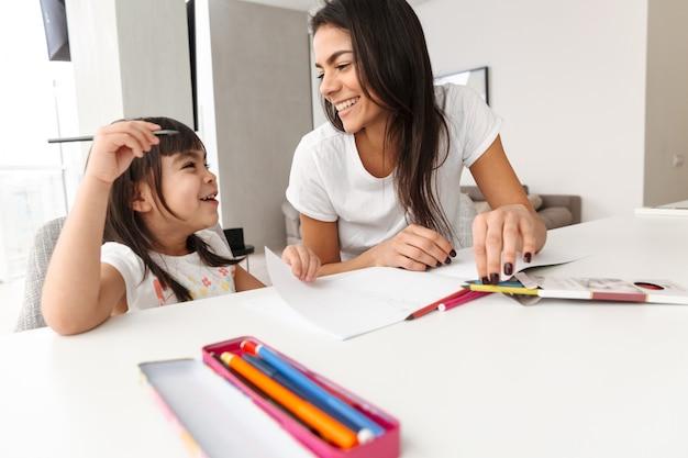 Portret van glimlachende familiemoeder en kind die tijd samen thuis doorbrengen, en het schilderen met markeerstiften trekken
