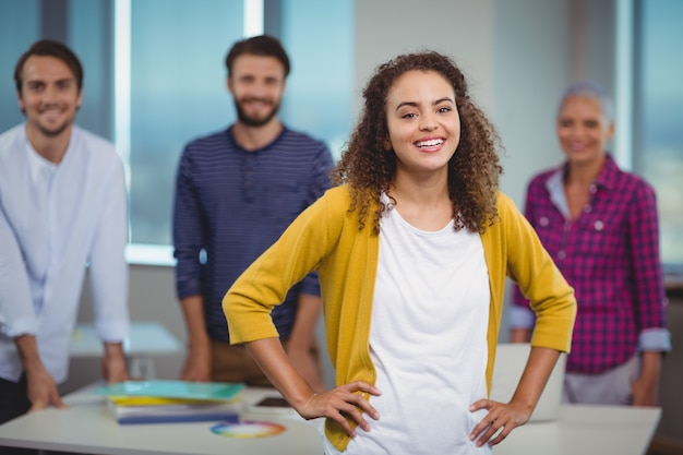 Portret van glimlachende grafisch ontwerper die zich met haar collega's bevindt
