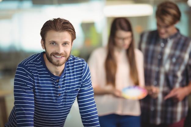 Portret van glimlachende grafisch ontwerper met collega's op achtergrond