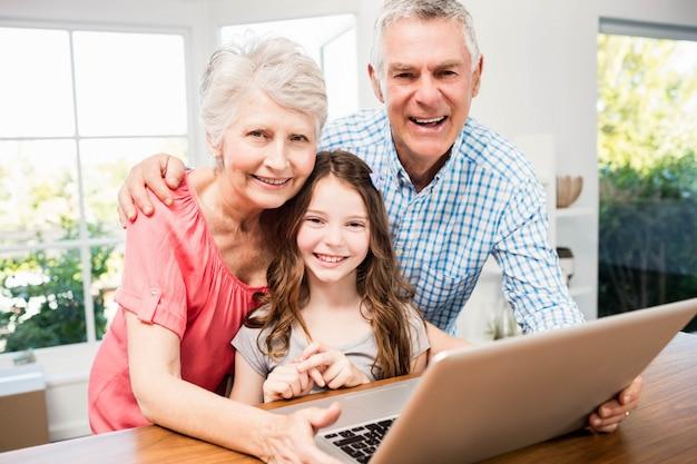 Portret van glimlachende grootouders en kleindochter die laptop thuis met behulp van
