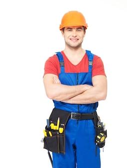 Portret van glimlachende handarbeider met hulpmiddelen op wit wordt geïsoleerd