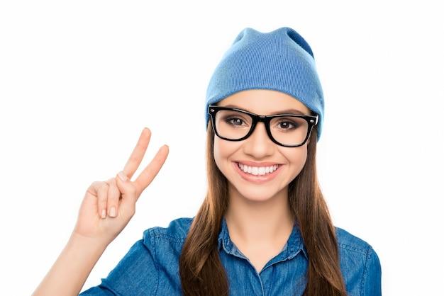 Portret van glimlachende hipster vrouw in glazen met twee vingers