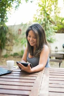 Portret van glimlachende japanse vrouw die tablet in openluchtcafé gebruikt. mooi meisje met bruin haar winkelen of online chatten, plezier maken, lezen, freelancer werken. koffie drinken