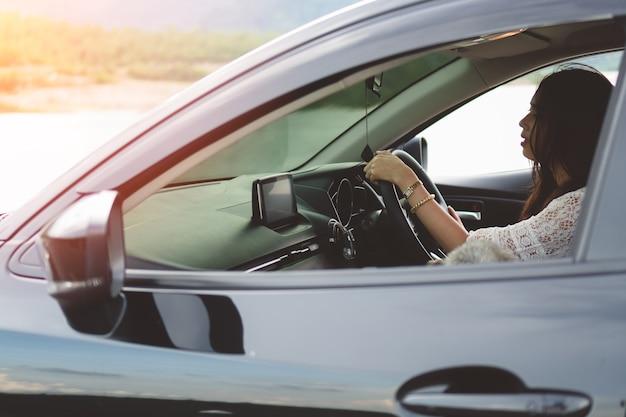 Portret van glimlachende jonge aziatische vrouw die een auto drijft.