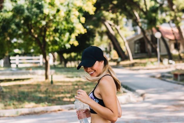 Portret van glimlachende jonge het waterfles die van de vrouwenholding zich in het park bevinden