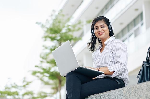 Portret van glimlachende jonge indische onderneemster in hoofdtelefoons die buiten zitten en op laptop werken