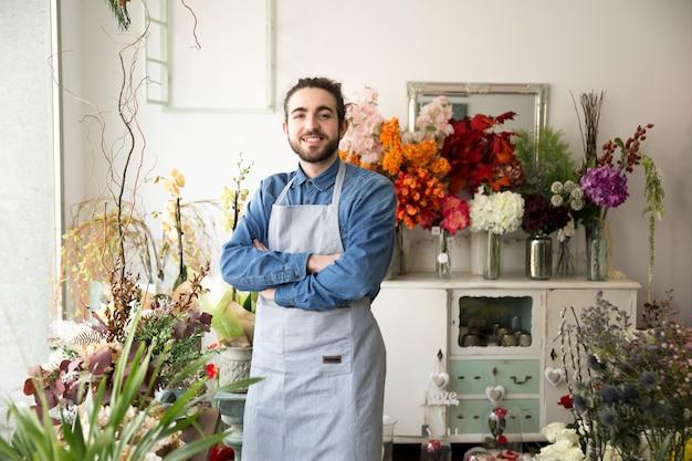 Portret van glimlachende jonge mannelijke bloemist met wapen dat in zijn bloemwinkel wordt gekruist