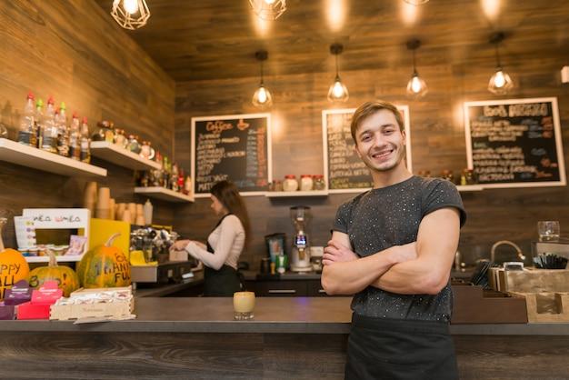 Portret van glimlachende jonge mannelijke coffeeshophouder