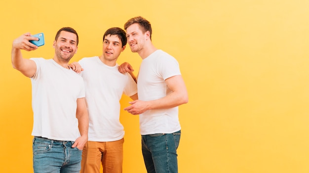 Portret van glimlachende jonge mannelijke vrienden die selfie op slimme telefoon tegen gele achtergrond nemen