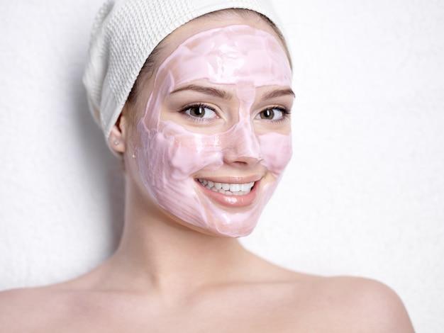 Portret van glimlachende jonge mooie vrouw met roze gezichtsschoonheidsmasker