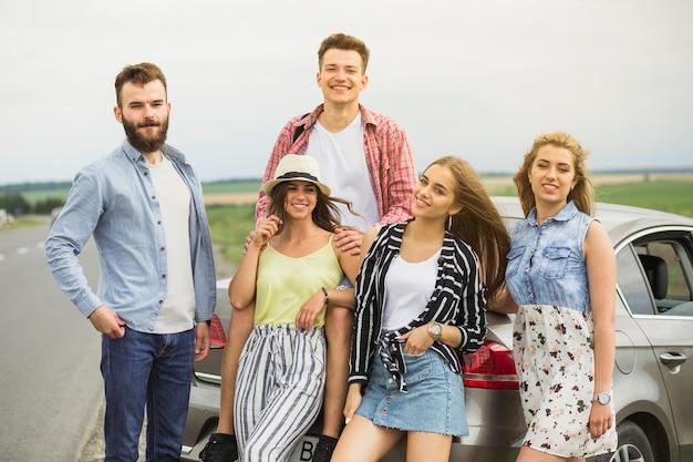 Portret van glimlachende jonge vrienden die zich dichtbij de auto bevinden
