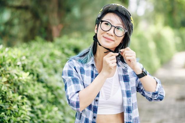 Portret van glimlachende jonge vrij chinese tiener vastmakende helm alvorens op fiets in park te berijden