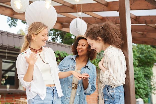 Portret van glimlachende jonge vrouw die verlovingsring toont aan vriendinnen tijdens openluchtpartij