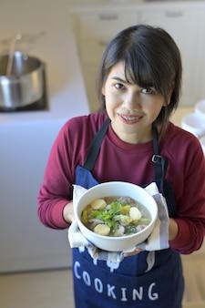 Portret van glimlachende jonge vrouw in moderne keuken en holding een kom soep met tofu