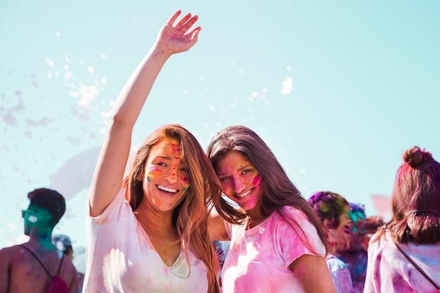 Portret van glimlachende jonge vrouwen die van het holifestival genieten