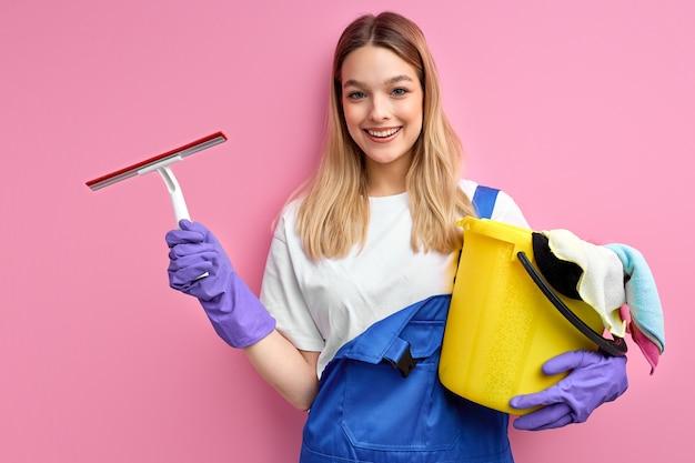 Portret van glimlachende jonge vrouwenhuisvrouw die in handschoenen reinigingsmiddeldingen geïsoleerd houden