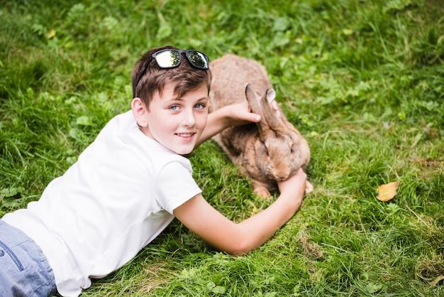 Portret van glimlachende jongen die op groen gras ligt dat zijn konijn behandelt