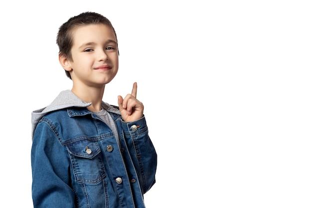 Portret van glimlachende jongen in spijkerjasje die omhoog wijst en naar dezelfde plaats kijkt, die pret op wit geïsoleerde achtergrond heeft