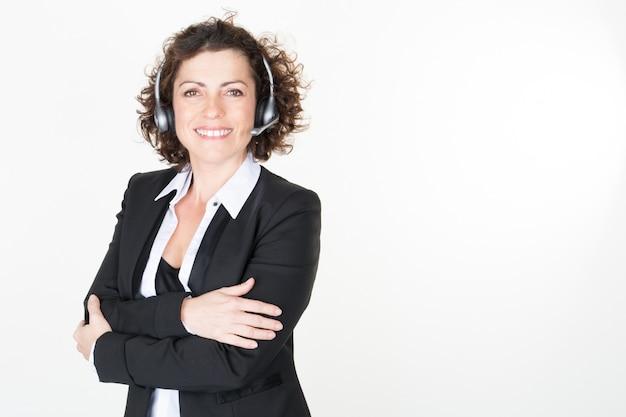 Portret van glimlachende kaukasische klantenservice en ondersteuningsvrouw die hoofdtelefoon in helder bureau draagt