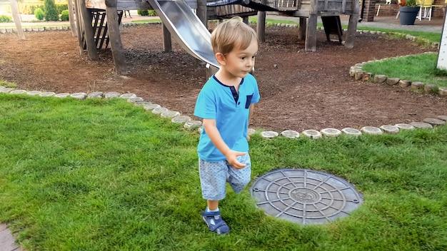Portret van glimlachende kleine jongen die op grasgazon bij park loopt
