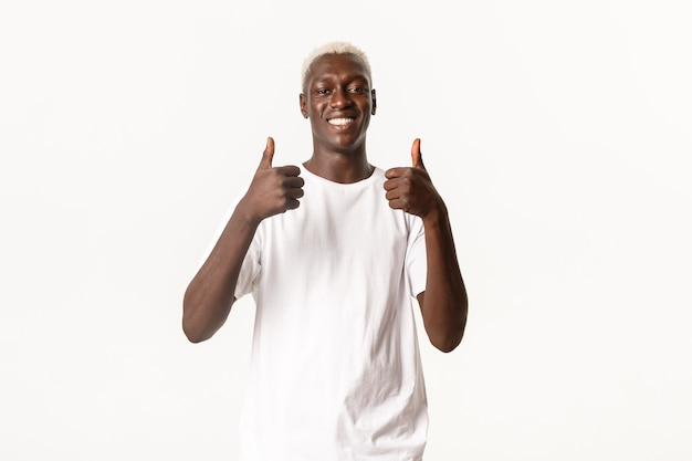 Portret van glimlachende knappe afro-amerikaanse man, tevreden kijkend, duim omhoog in goedkeuring, zoals iets