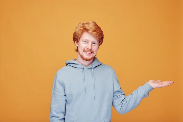 Portret van glimlachende knappe roodharige kerel die opzij gebaart terwijl hij nieuw product op sinaasappel voorstelt