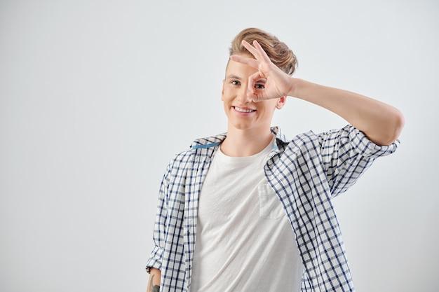 Portret van glimlachende knappe tiener die ok gebaar maakt en voorzijde bekijkt, geïsoleerd op lichtgrijs