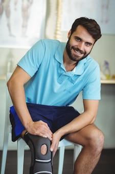 Portret van glimlachende man met knieblessure