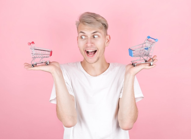 Portret van glimlachende man met mini winkelmandjes op roze