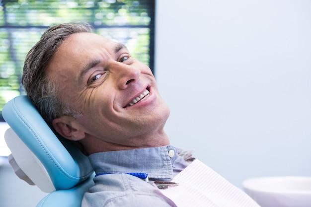 Portret van glimlachende man zittend op een stoel