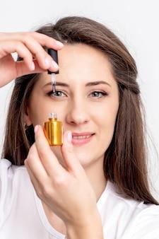 Portret van glimlachende manicuremeester houdt gouden nagellakfles over haar oog op witte muur