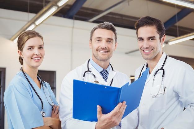 Portret van glimlachende mannelijke artsen die klemborden houden terwijl het werken
