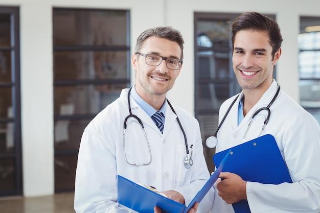 Portret van glimlachende mannelijke artsen die klemborden houden