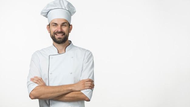 Portret van glimlachende mannelijke chef-kok in witte die eenvormig over witte achtergrond wordt geïsoleerd