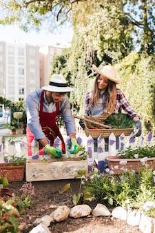 Portret van glimlachende mannelijke en vrouwelijke tuinman die in de tuin werken
