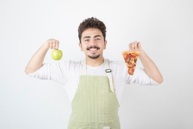 Portret van glimlachende mannelijke kok die pizza en groene appel op wit toont