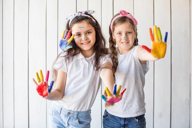 Portret van glimlachende meisjes die hoofdband dragen die kleurrijke geschilderde handen tonen tegen houten muur