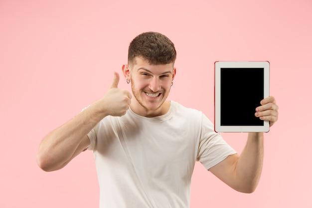 Portret van glimlachende mens die op laptop met leeg scherm richt dat op roze studioachtergrond wordt geïsoleerd. en reclame concept.
